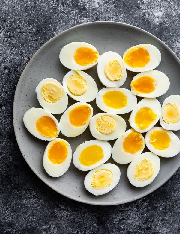 Lots of halved hard and soft boiled eggs laying on a gray plate