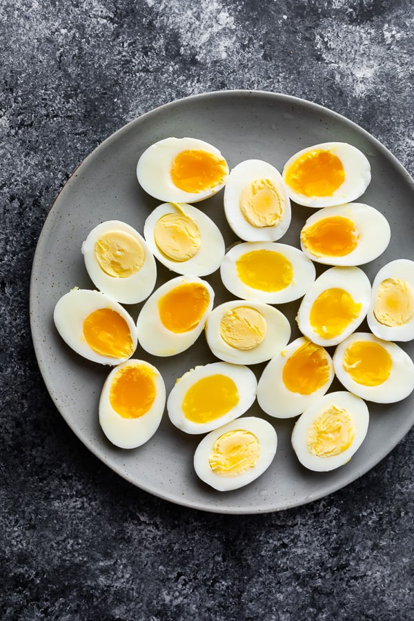 hard and soft boiled eggs cut in half and arranged on a plage