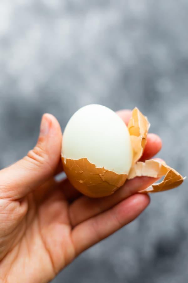 hand holding a half-peeled hard boiled egg