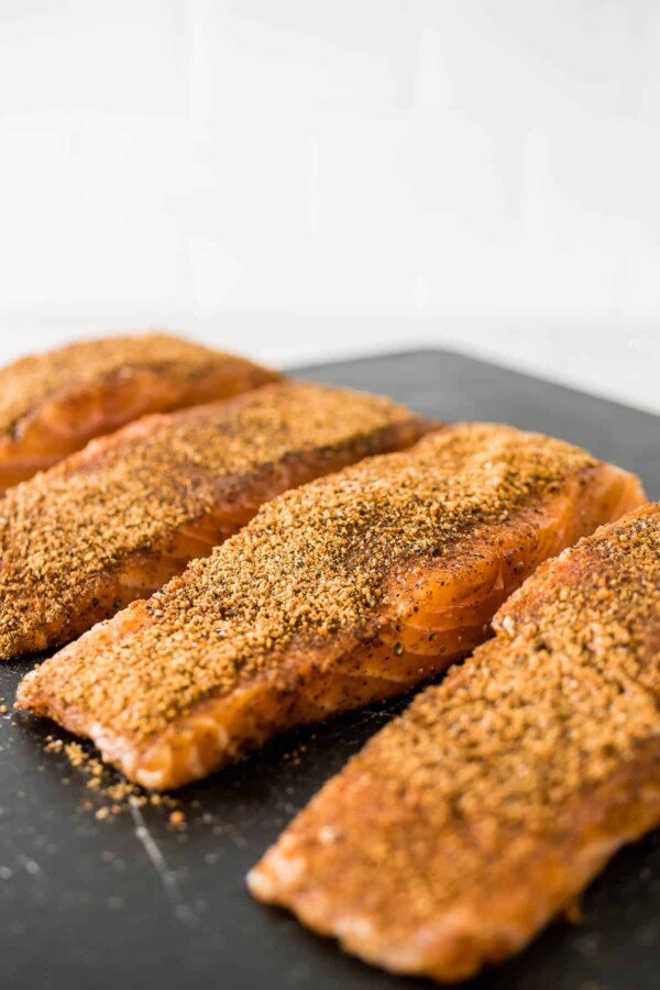 salmon on cutting board with rub on it; before cooking