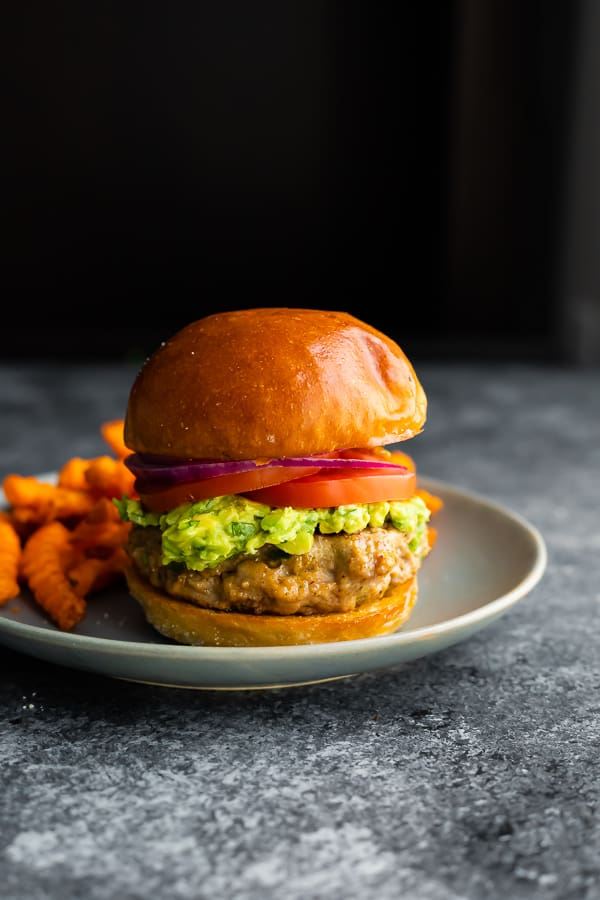 side angle view of southwestern turkey burgers on a plate with sweet potato fries