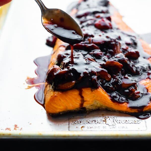 Salmon with a spoon drizzling strawberry balsamic reduction on top