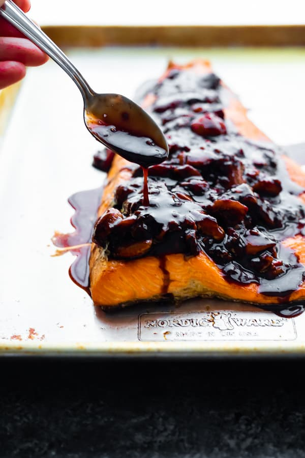 spooning strawberry balsamic sauce over salmon