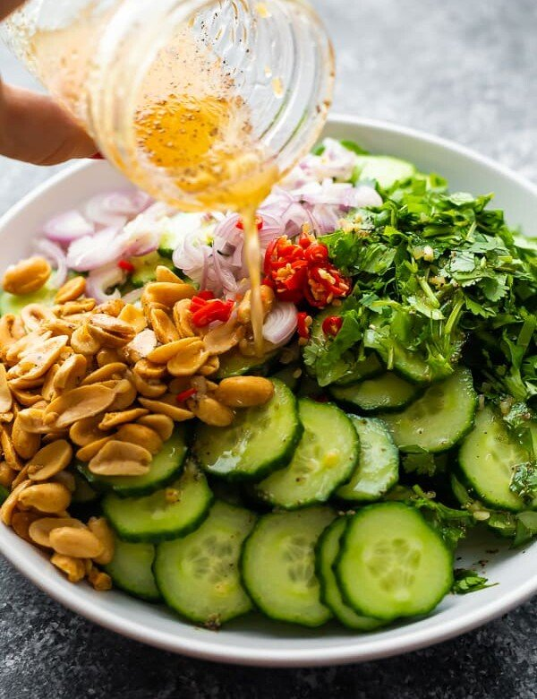 Crunch Asian cucumber salad in a white bowl with dressing in a mason jar being drizzled on top