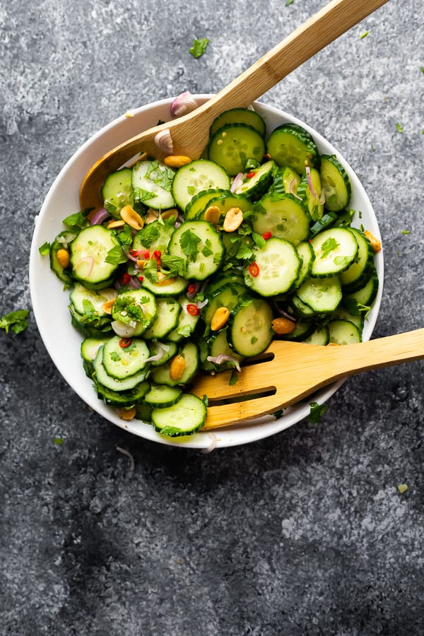 Overhead shot of Asian Cucumber Salad in a large white bowl with two wooden tongs