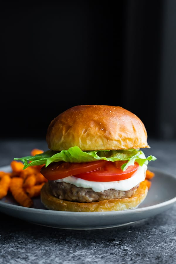 side angle view of turkey burger on plate with sweet potato fries