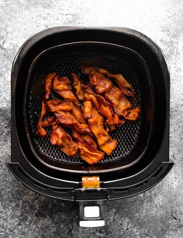 overhead view of bacon in an air fryer basket