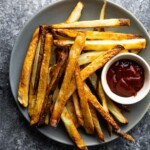 overhead view of air fryer french fries on a plate with ketchup