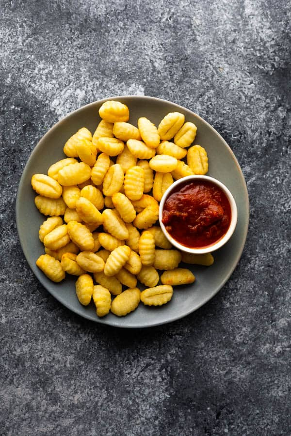 overhead view of air fryer gnocchi on plate with bowl of marinara sauce