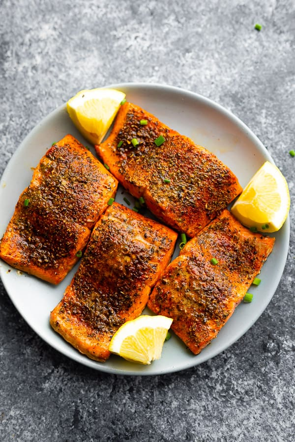 overhead view of plate with four air fryer salmon portions and lemon wedges