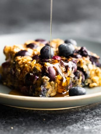 close up shot of a slice of blueberry baked oatmeal with syrup drizzled on top