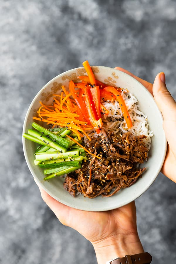 hands holding honey garlic beef rice bowl
