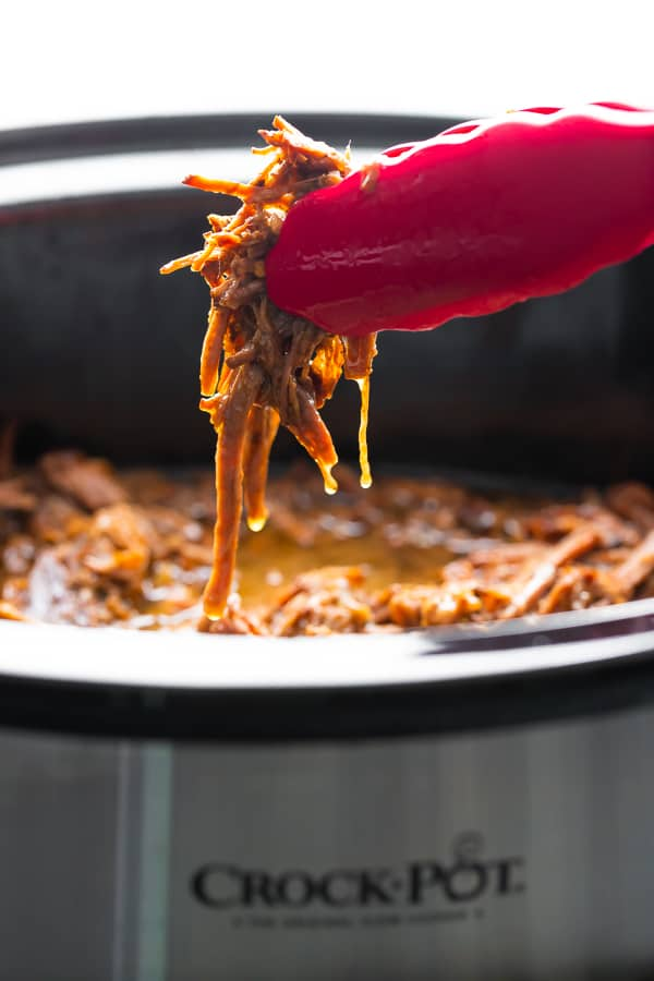 tongs pulling honey garlic beef out of the slow cooker