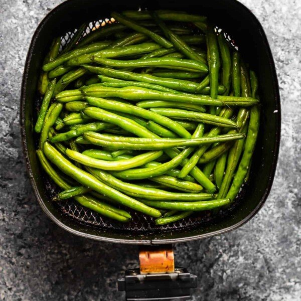 overhead view of green beans in air fryer after cooking through