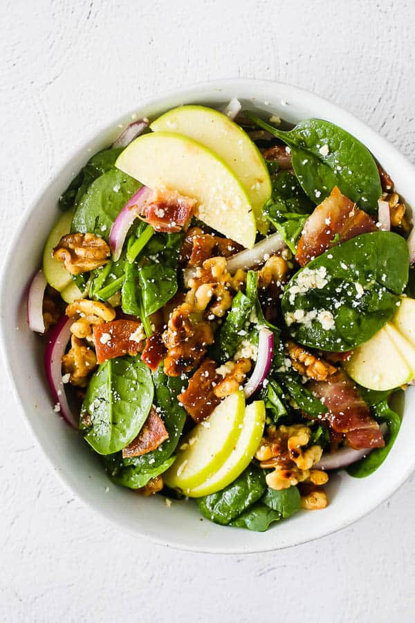 bowl with apple bacon spinach salad mixed up