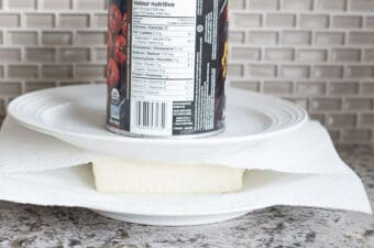 tofu pressed between plates with can on top