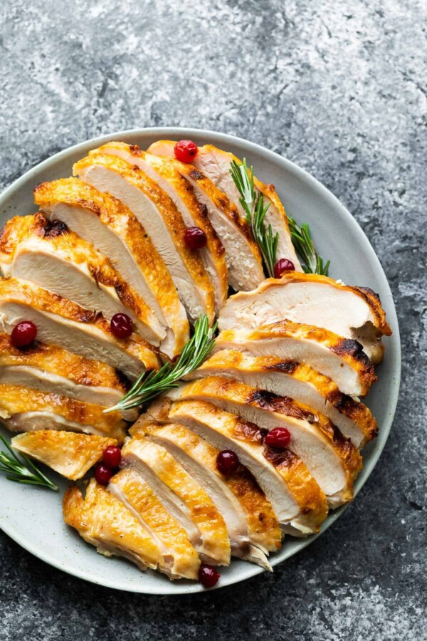platter with sliced instant pot turkey breast, rosemary and cranberries