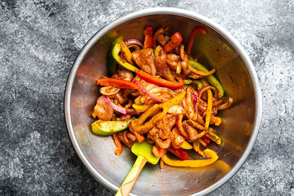 chicken and bell peppers in a bowl mixed with fajita seasoning