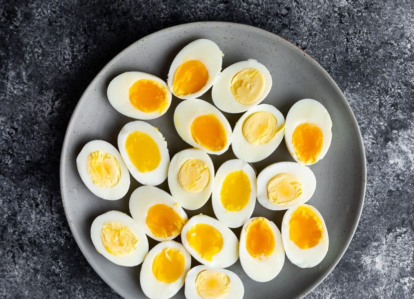 overhead of hard and soft boiled eggs on grey plate