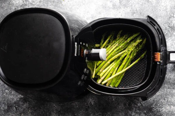 overhead view of asparagus in air fryer with basket pulled out
