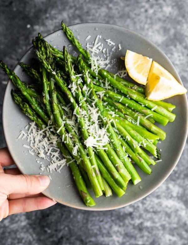 holding plate of asparagus with parmesan cheese