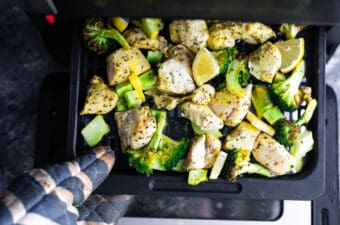 Oven mitt pulling the lemon pepper chicken and broccoli out of the air fryer