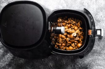 uncooked mushrooms in an air fryer basket