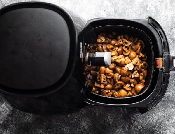 uncooked mushrooms in an air fryer basket
