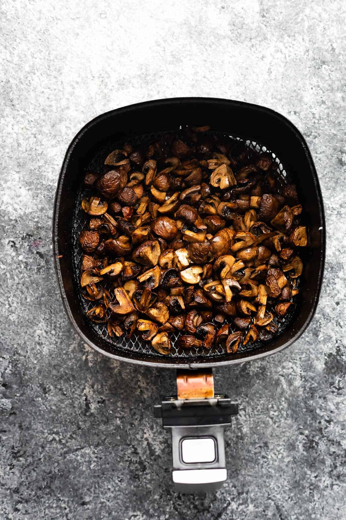 overhead view of cooked mushrooms in air fryer basket
