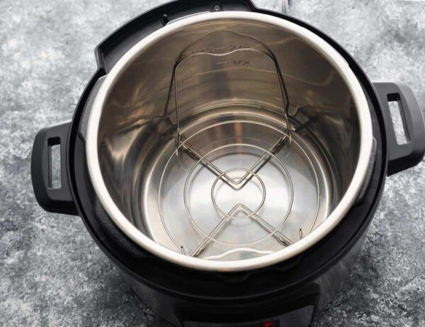 instant pot with water and trivet in the insert