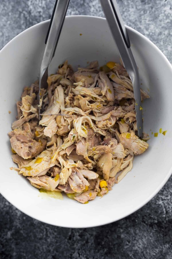 shredded chicken in a bowl with tongs