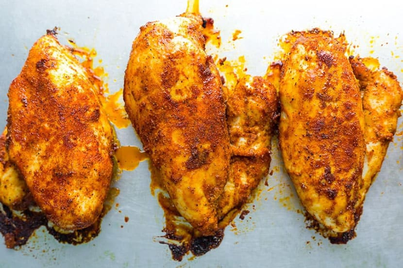 three baked chicken breasts on a sheet pan