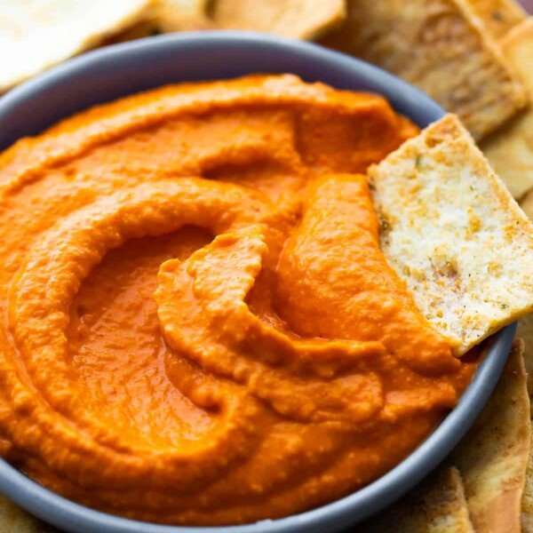 close up shot of roasted red pepper hummus with pita chip