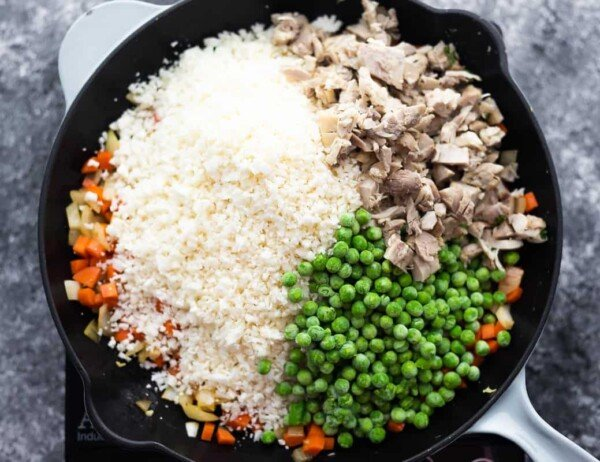 riced cauliflower, frozen peas and cooked chicken added to a skillet