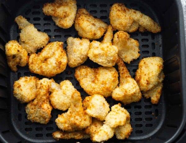 crispy and golden breaded cauliflower in an air fryer basket