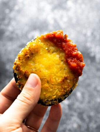hand holding air fried eggplant dipped in marinara sauce