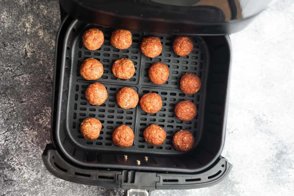 uncooked meatballs in air fryer basket