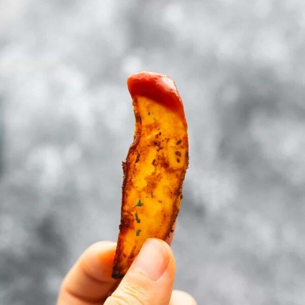 hand holding potato wedge dipped in ketchup