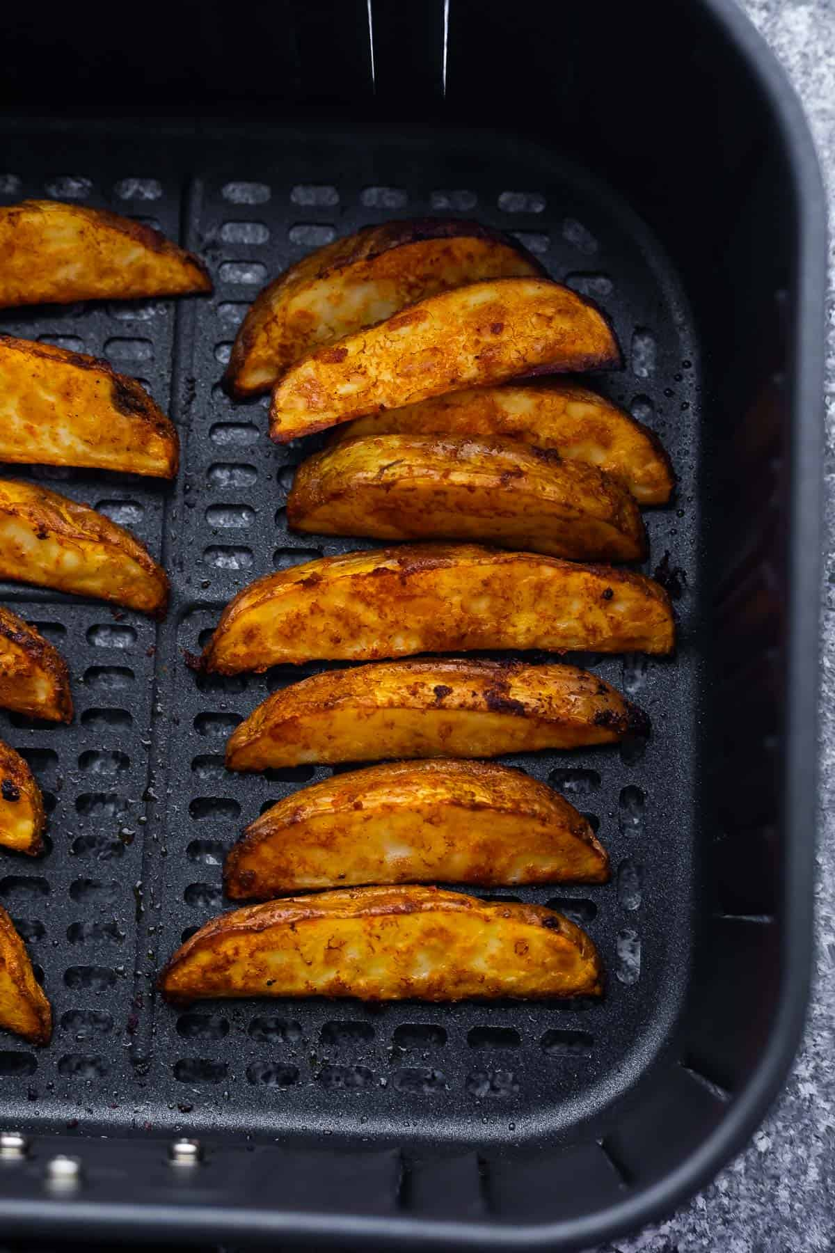 cooked potato wedges arranged in air fryer basket