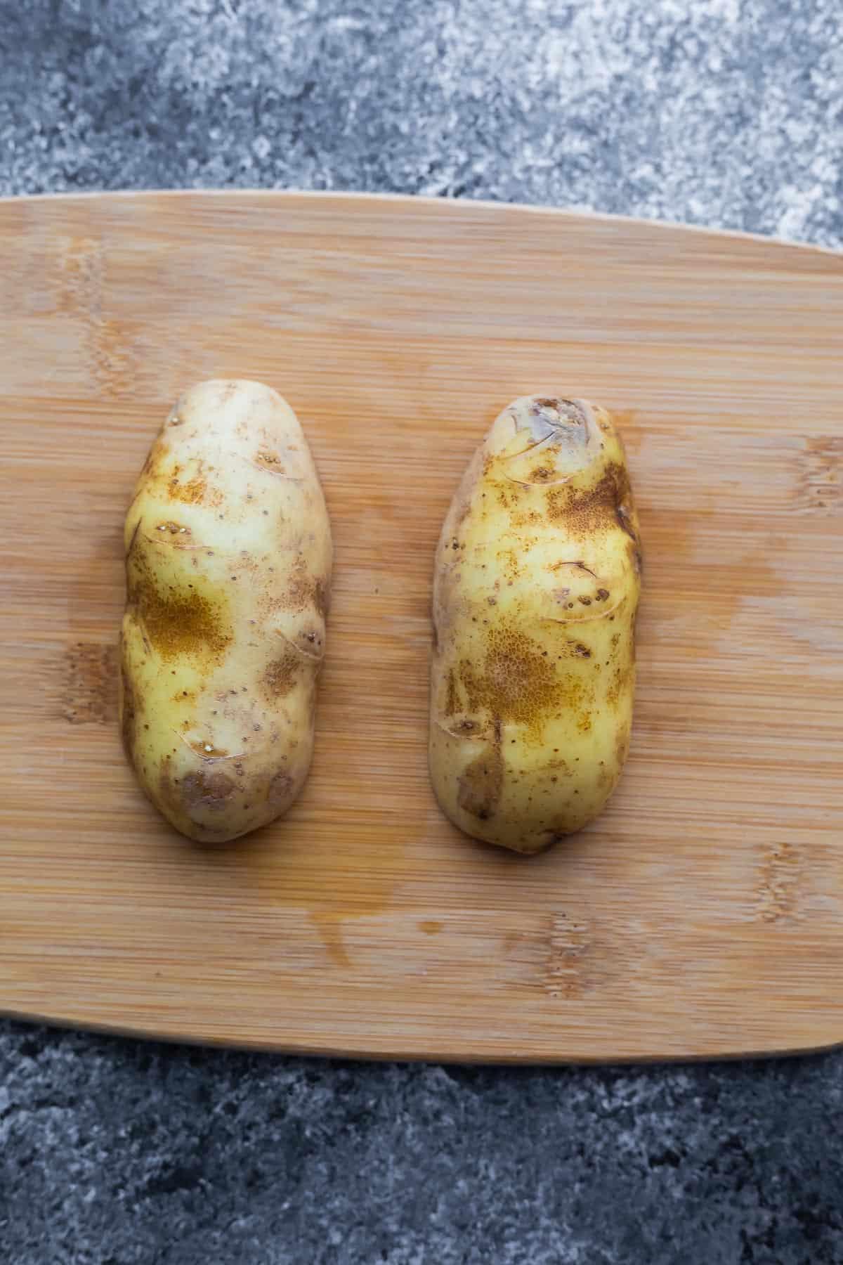 russet potato cut in half (cut sides down) on cutting board