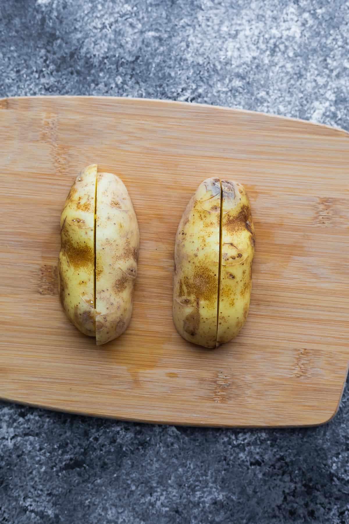 russet potato cut in quarters (cut side down) on cutting board
