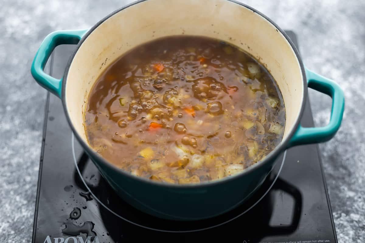 simmering pot of beef barley soup on burner