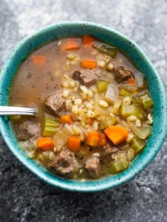 close up shot of beef barley soup with a spoon