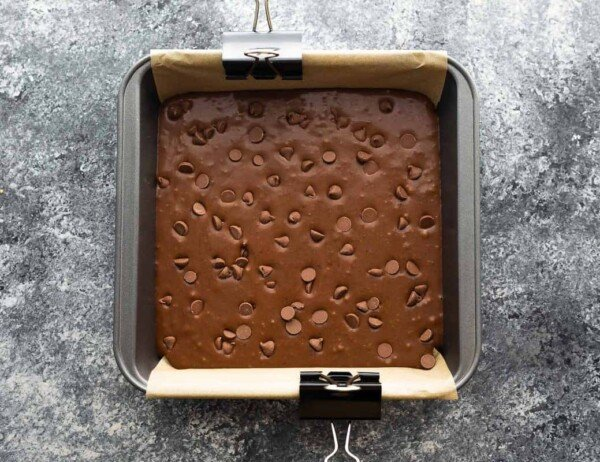 overhead view of black bean brownies in parchment-lined baking pan before baking