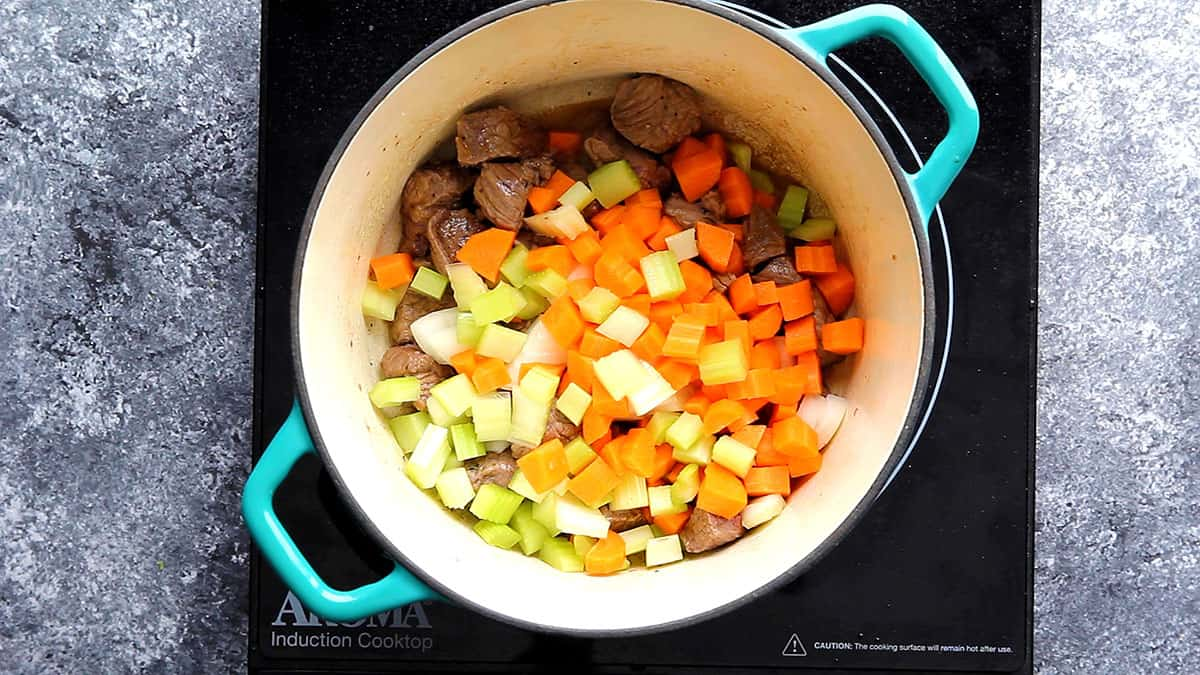 onions, celery and carrot added to beef in a pot