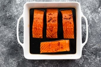 4 salmon fillets (unbaked) arranged in square baking dish with teriyaki sauce