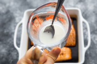 cornstarch water slurry in measuring cup about to be poured into baking dish with salmon and teriyaki sauce