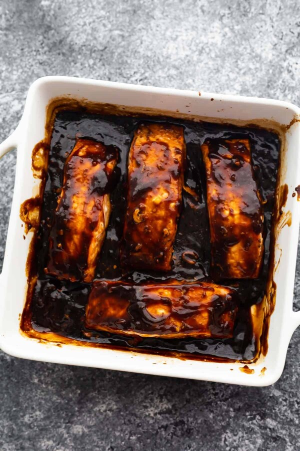 four baked salmon fillets arranged in baking dish with thickened teriyaki sauce