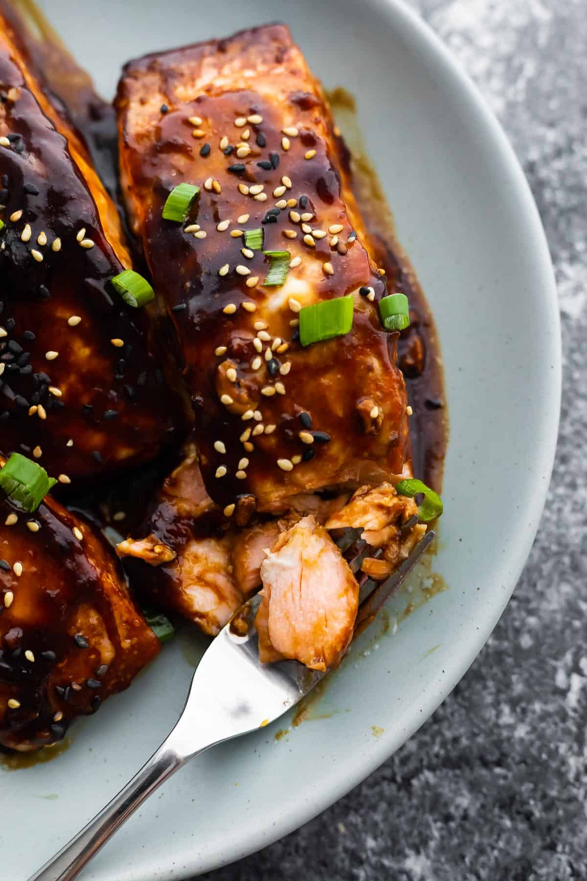 close up shot of teriyaki glazed salmon on plate with fork showing inside of salmon