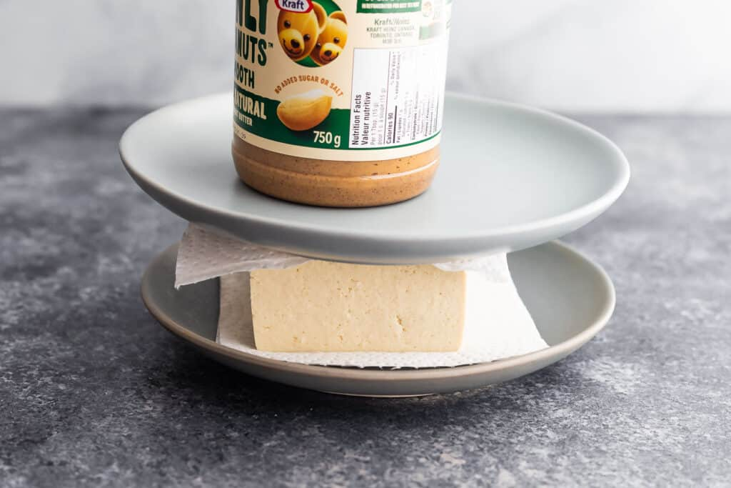 tofu pressed between paper towels, plates and with a jar of peanut butter on top